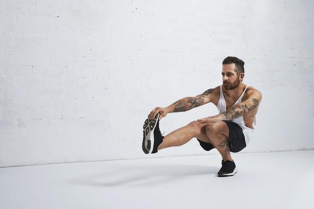 L'allenatore di ginnastica ritmica tatuata brutale mostra che l'esercizio muove uno squat della gamba, isolato sul muro di mattoni bianco Foto Gratuite