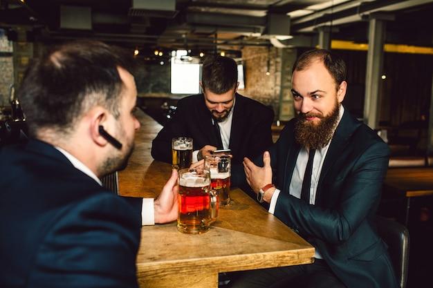 Позитивные молодые bsinessmen в костюмах сидят вместе за столом. они держат кружки пива. парень впереди с наушниками в ухе. мужчины в баре. Premium Фотографии