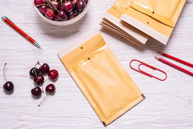 チェリー、夏のコンセプトと木製のテーブルの上のバブルの封筒 Premium写真