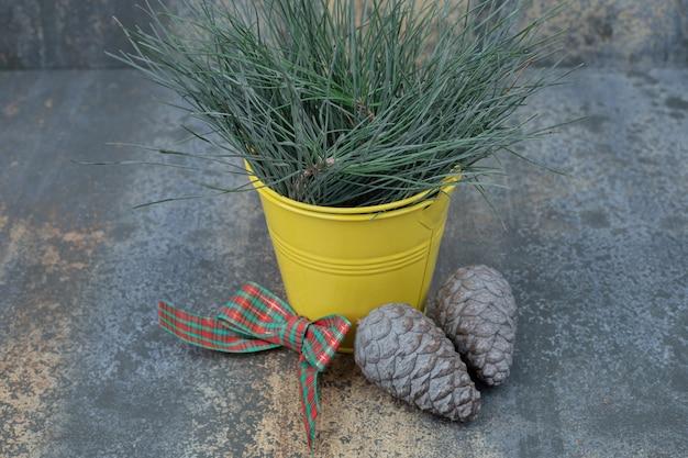 大理石のテーブルに弓と松ぼっくりで飾られた草のバケツ。高品質の写真 無料写真