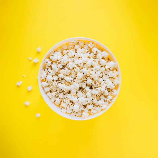 Bucket of popcorn on yellow Premium Photo