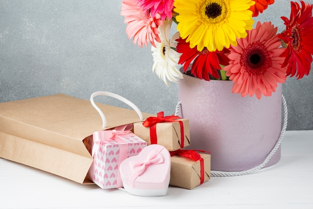 Bucket with gerbera flowers and gift papers and boxes Free Photo