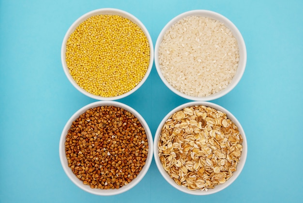 Гречка, просо, рис и пшеница на синем фоне Premium Фотографии