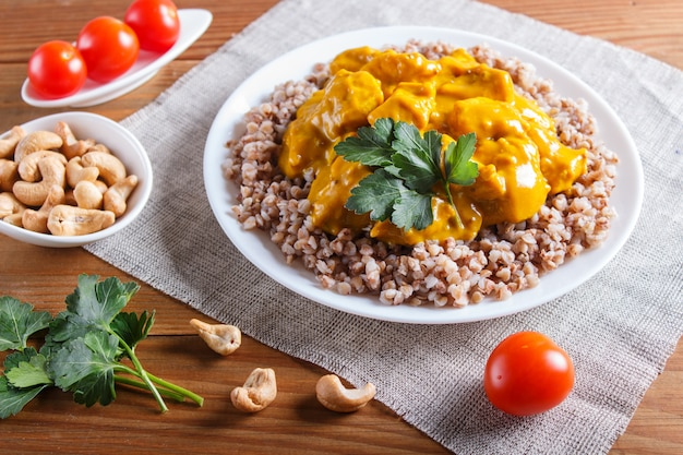 Buckwheat with chicken curry sauce with cashew on brown wooden surface. Premium Photo