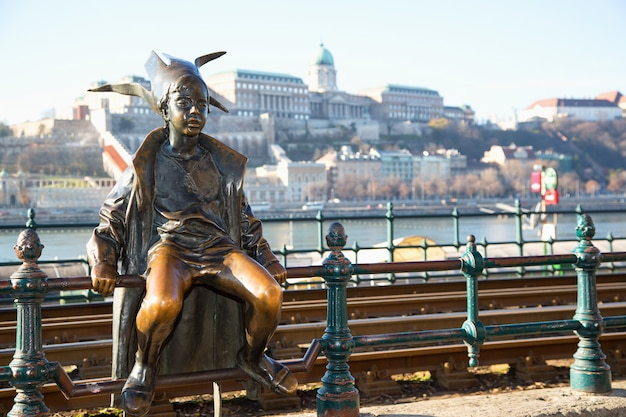 Budapest attractions. little princess perched by the tram rails on the pest, with buda castle, landmark of hungary capital city. budapest, hungary. Premium Photo