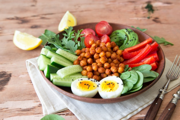 Buddha bowl, healthy and balanced food. fried chickpeas, cherry tomatoes, cucumbers, paprika, eggs, spinach, arugula Premium Photo