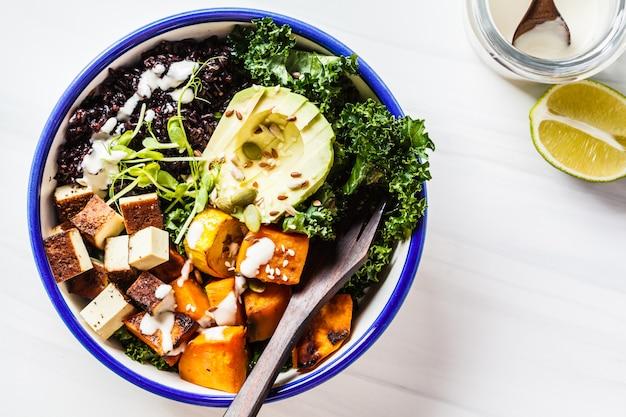 Buddha bowl salad with black rice, avocado, tofu, sweet potato, kale and tahini dressing Premium Photo