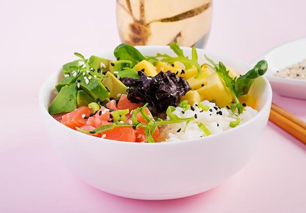 Buddha bowl with rice, mango, avocado and salmon. healthy food. Premium Photo