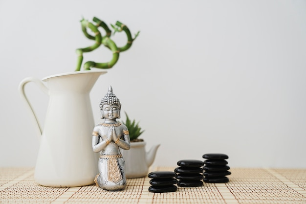 Buddha figure in front of bamboo plant and volcanic stones Free Photo