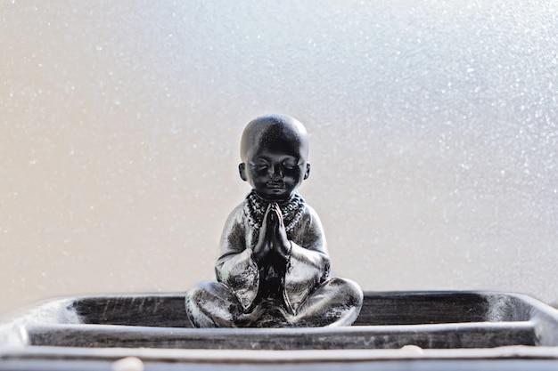 Статуя будды в позе лотоса против стекла Premium Фотографии