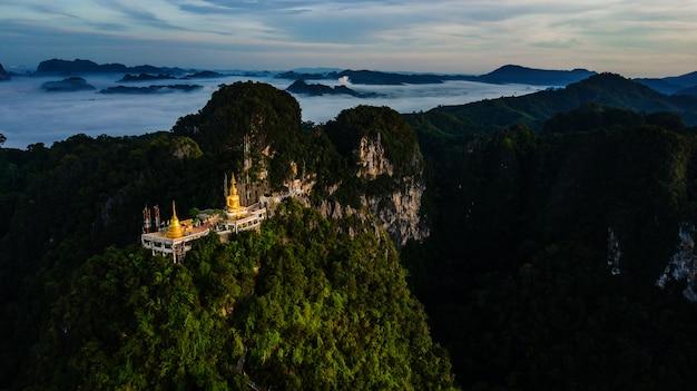 Buddha on the top mountain of wat tham seua (tiger cae) , krabi,thailand Premium Photo