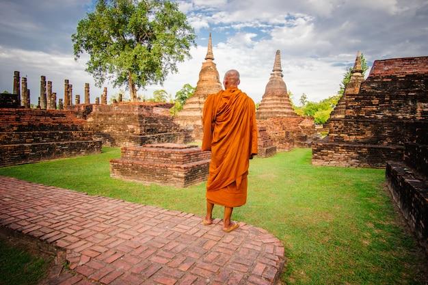 Buddhist monk in ancient ruins in ayutthaya, thailand. Premium Photo