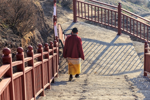 Buddhist nun walking down stairway at larung gar in a warm and foggy morning time, sichuan Premium Photo