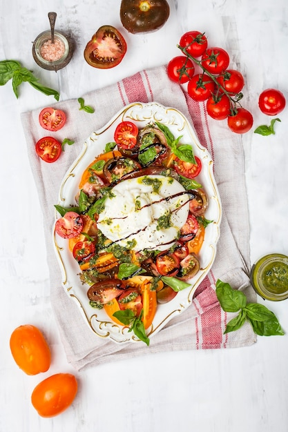 Buffalo burrata cheese with fresh raw tomatoes and basil leaves Premium Photo