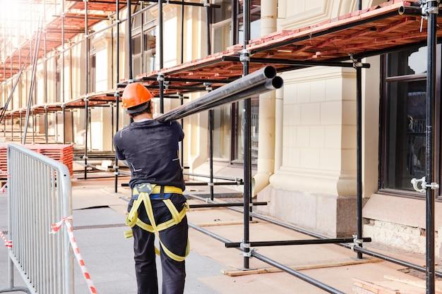 Строитель несет на плече стальную балку. строительная площадка, строительство и реконструкция здания. Premium Фотографии