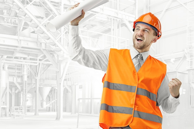 The builder in a construction vest and orange helmet smiling as winner against industrial background. safety specialist, engineer, industry, architecture, manager, occupation, businessman, job concept Free Photo