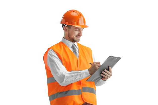 The builder in a construction vest and orange helmet standing on white wall. safety specialist, engineer, industry, architecture, manager, occupation, businessman, job concept Free Photo