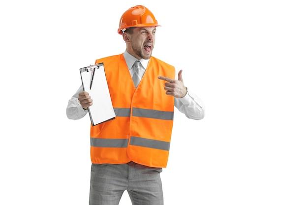 Il costruttore in un giubbotto di costruzione e casco arancione in piedi sul muro bianco. specialista della sicurezza, ingegnere, industria, architettura, manager, occupazione, uomo d'affari, concetto di lavoro Foto Gratuite