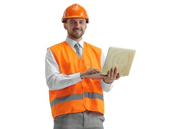 Il costruttore in un giubbotto di costruzione e un casco arancione con laptop. specialista della sicurezza, ingegnere, industria, architettura, manager, occupazione, uomo d'affari, concetto di lavoro Foto Gratuite