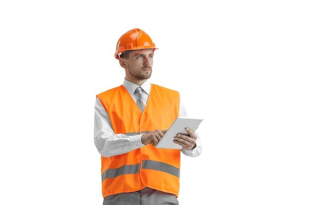 Il costruttore in un giubbotto di costruzione e un casco arancione con tablet. specialista della sicurezza, ingegnere, industria, architettura, manager, occupazione, uomo d'affari, concetto di lavoro Foto Gratuite