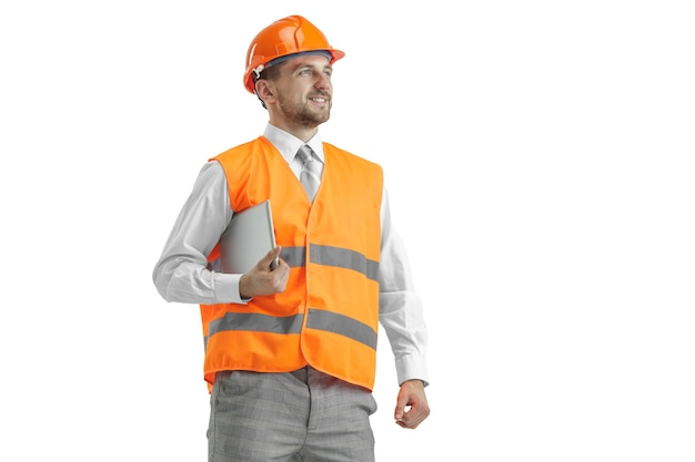 The builder in a construction vest and an orange helmet with tablet. safety specialist, engineer, industry, architecture, manager, occupation, businessman, job concept Free Photo