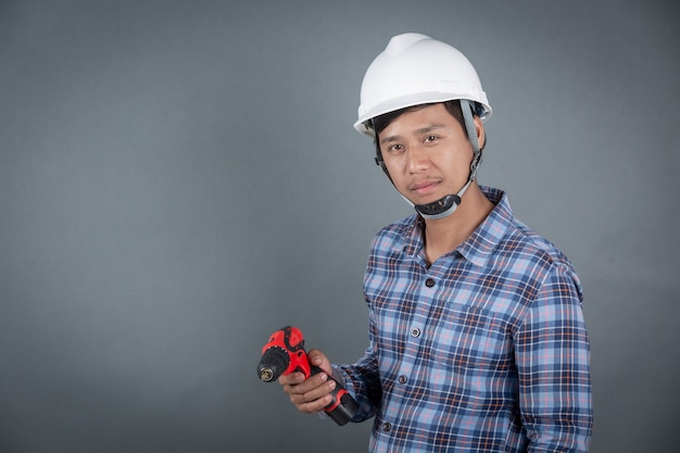 Builder holding drill on grey background Free Photo