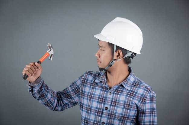 Builder holding hammer on grey background. Free Photo