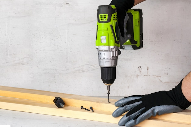 The builder holds in his hand an electric screwdriver on the background of a concrete wall. screws screw into a wooden beam. diy Premium Photo