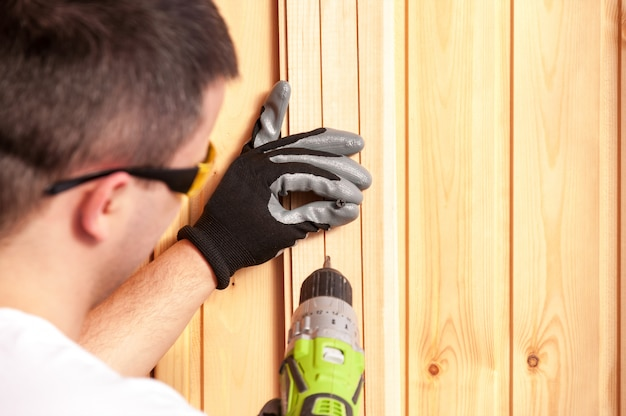 The builder holds in his hand an electric screwdriver on the background of a concrete wall. Premium Photo