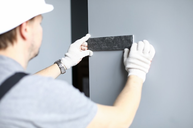 手袋とヘルメットのビルダーは、アパートの壁のタイルの色を選びます。男は壁に建築材料のサンプルを適用します Premium写真