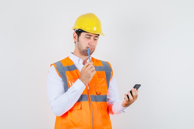 Builder man holding pencil while looking at smartphone in shirt, uniform and looking pensive , front view. Free Photo