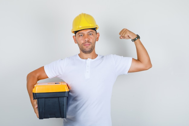 ツールボックスを押しながらtシャツ、ヘルメットで筋肉を見せ、自信を持って、正面を見てビルダー男。 無料写真