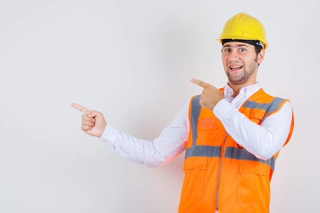 Builder man pointing fingers to side in shirt, uniform and looking cheerful , front view. Free Photo