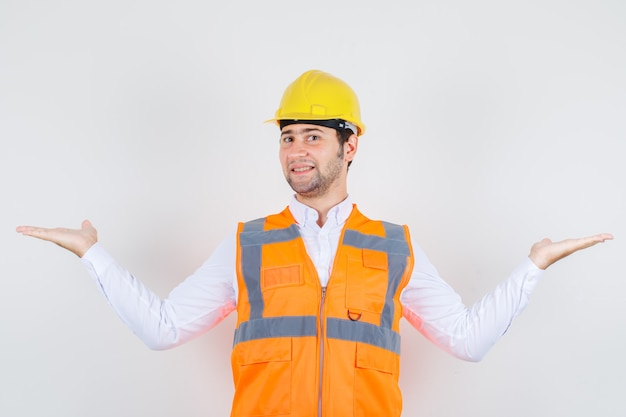 Builder man in shirt, uniform spreading arms wide like catching something and looking happy , front view. Free Photo