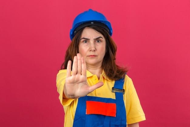 孤立したピンクの壁を越えて深刻で自信を持って式防衛ジェスチャーで一時停止の標識をやって開いて手で立っている建設の制服と安全ヘルメット立っているビルダーの女性 無料写真