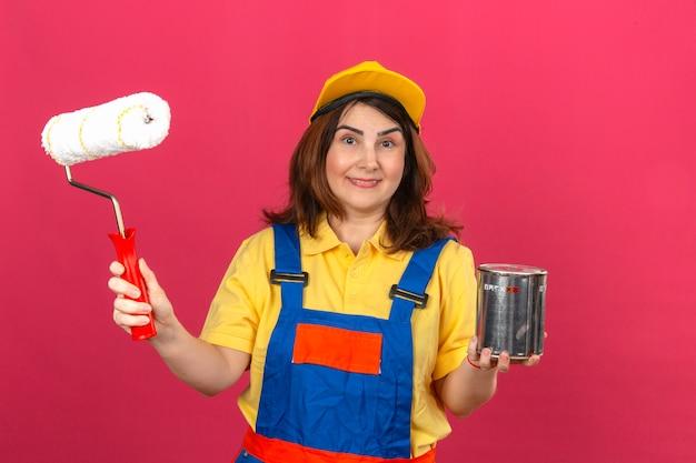 ビルダーの女性が身に着けている建設ユニフォームとペイントローラーと塗料を保持している黄色のキャップは、孤立したピンクの壁に幸せそうな顔で笑うことができます。 無料写真