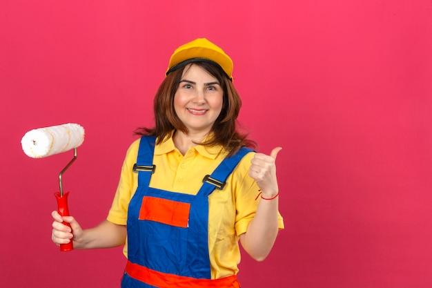 ペイントローラーを押しながら孤立したピンクの壁を越えて陽気な笑顔を親指を現して建設制服と黄色の帽子を身に着けているビルダー女性 無料写真