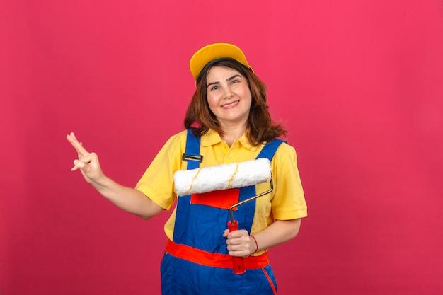 孤立したピンクの壁に指で陽気に番号3を示す笑みを浮かべてペイントローラーを保持している建設の制服と黄色のキャップを身に着けているビルダー女性 無料写真