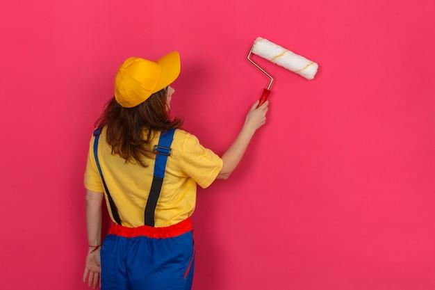 ビルダーの女性が彼女の背中にペイントローラーで立っていると孤立したピンクの壁に絵を描く建設制服と黄色のキャップを着て 無料写真