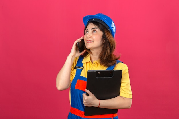 Builder woman wearing construction uniform and safety helmet holding clipboard while talking on mobile phone looking up with smile on face over isolated pink wall Free Photo