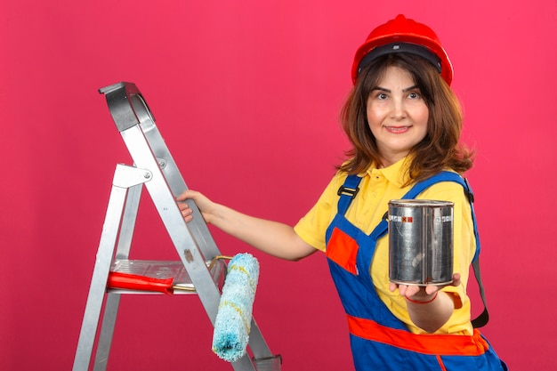 Uniforme edile d'uso della donna del costruttore e casco di sicurezza che stanno sulla scala con il sorriso sul fronte che allunga fuori la latta della pittura sopra la parete rosa isolata Foto Gratuite