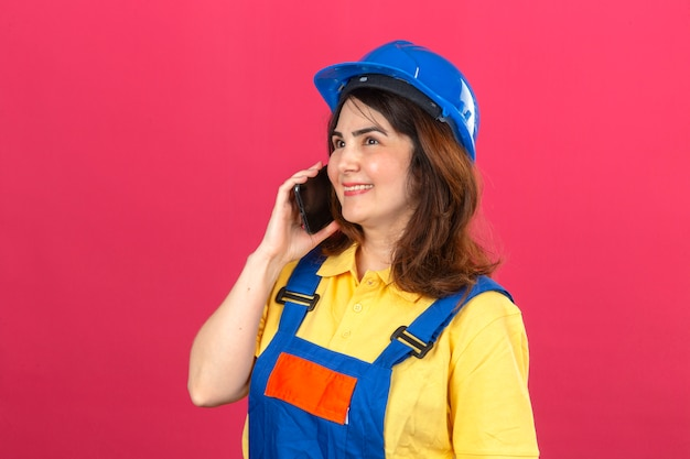 Builder woman wearing construction uniform and safety helmet talking on mobile phone smiling cheerful over isolated pink wall Free Photo