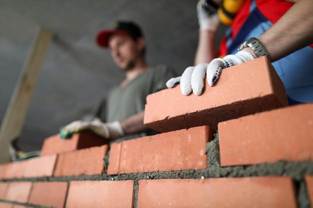 ビルダーは壁のレンガとセメントの技術を作る Premium写真