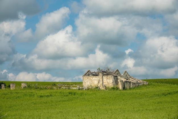 Edificio costruito su un campo verde sotto un cielo pieno di nuvole durante il giorno Foto Gratuite