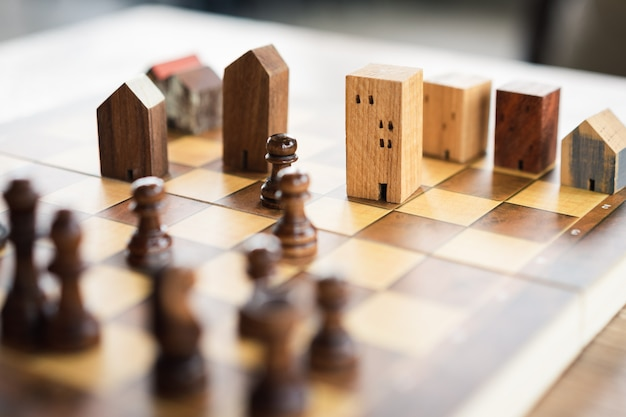 Building and house models in chess game. Premium Photo