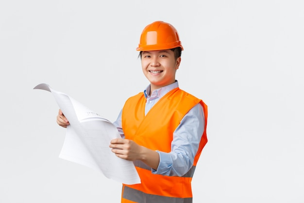 Building sector and industrial workers concept. confident smiling asian architect, chief engineer in helmet and reflective jacket holding blueprints, inspecting enterprise, white wall Free Photo