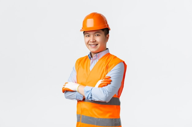 Building sector and industrial workers concept. confident young asian engineer, construction manager in reflective clothes and helmet, cross arms and smiling sassy, ensuring quality, white wall Free Photo