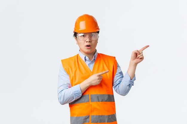 Building sector and industrial workers concept. impressed and amazed asian construction manager, engineer in helmet and reflective clothing pointing upper right corner, white wall Free Photo
