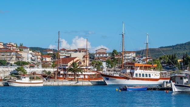 여러 녹지가있는 언덕에 위치한 건물, 전경에 정박중인 요트가있는 부두, Neos Marmaras, 그리스 무료 사진