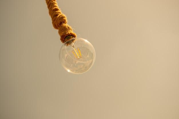 電球がロープから淡い茶色にぶら下がっています 無料写真